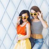 Het mooie jonge blonde en het brunette van paar modieuze meisjes in een heldere gele kleding en zonnebril die en voor ca stellen  Royalty-vrije Stock Afbeeldingen