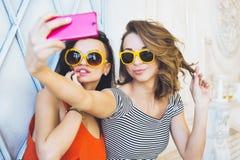 Het mooie jonge blonde en het brunette van paar modieuze meisjes in een heldere gele kleding en zonnebril die en voor ca stellen  Stock Afbeelding