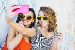 Het mooie jonge blonde en het brunette van paar modieuze meisjes in een heldere gele kleding en zonnebril die en voor ca stellen  Stock Afbeeldingen