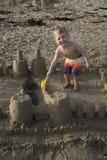 Het mooie jonge blonde jongen spelen op strand in een zandkasteel Stock Foto's