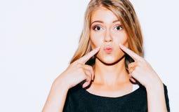 Het mooie jonge blonde meisje stellen in Sweatshirt en witte borrels en rode lippenkus  Zij richt een vinger op haar lippen Sluit Stock Afbeeldingen
