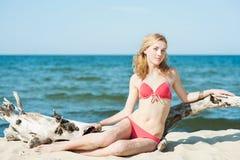 Het mooie jonge blonde vrouw sunbatching op een strand stock fotografie