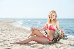 Het mooie jonge blonde vrouw sunbatching op een strand royalty-vrije stock afbeeldingen