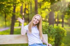 Het mooie jonge blondemeisje golven, heet welkom, zit in het park op de bank royalty-vrije stock afbeelding