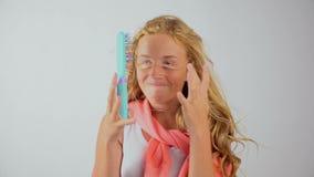 Het mooie jonge blondemeisje kan niet haar lang haar, slordig kapsel stileren stock footage