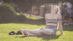 Het mooie jonge blondemeisje ontspant op een gras in een stadspark, centraal park op een zonnige dag Stock Afbeelding