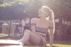 Het mooie jonge blondemeisje ontspant op een gras in een stadspark, centraal park op een zonnige dag Stock Foto's