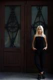 Het mooie jonge blondemeisje stellen op de achtergrond van de deuren van Bourgondië Sexy vrouw in een zwarte kleding Het meisje o Royalty-vrije Stock Afbeelding