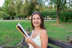 Het mooie jonge brownhairmeisje leest het boek en geniet van de geur van een verse gedrukte boekzitting op de bank in het park royalty-vrije stock foto