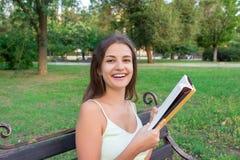 Het mooie jonge brownhairmeisje leest het boek en geniet van de geur van een verse gedrukte boekzitting op de bank in het park stock foto's