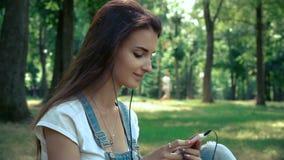 Het mooie jonge brunette neemt oortelefoons in haar oren op en luistert aan muziek stock video