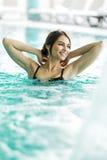 Het mooie jonge donkerbruine ontspannen in een zwembad Stock Foto's