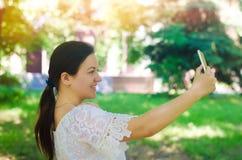 Het mooie jonge Europese meisjesbrunette neemt een beeld van zich en maakt selfie in het stadspark mensen, levensstijl, die binne royalty-vrije stock foto