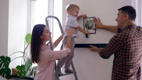 Het mooie jonge geitje met meetlint helpt baren en de vader hangt plank met beeld op muur na reparatie in vlakte stock videobeelden