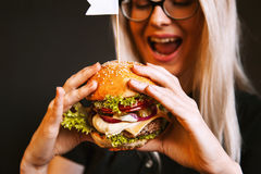 Het mooie jonge, gezonde meisje houdt een smakelijke grote hamburger met rundvleeskotelet Stock Foto