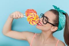Het mooie jonge hipstermeisje geniet van snoepje Stock Afbeeldingen