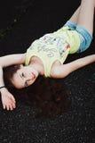 Het mooie jonge hipstermeisje ligt in het midden van asfaltweg, Royalty-vrije Stock Fotografie