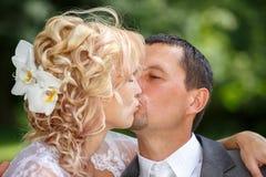 Het mooie jonge huwelijkspaar kussen Stock Afbeelding