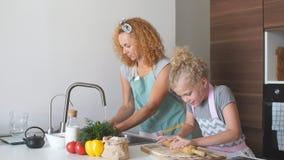 Het mooie jonge mamma en haar leuke kleine dochter spelen en glimlachen terwijl thuis het bakken in keuken stock videobeelden