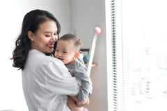 Het mooie jonge mamma speelt met haar leuke baby en glimlacht terwijl thuis status dichtbij het venster royalty-vrije stock foto's