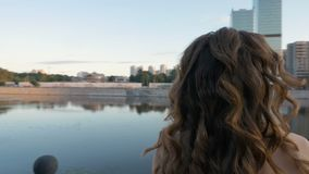 Het mooie jonge meisje bekijkt het water, die zich op de stadswaterkant bevinden stock videobeelden