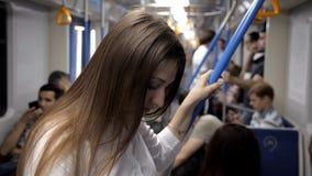 Het mooie jonge meisje berijdt de metro houdend op leuning het denken stock footage