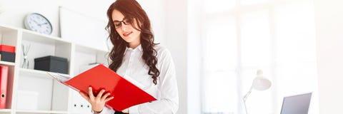 Het mooie jonge meisje bevindt zich in bureau, die op bureau en rollen door rode omslag met documenten leunen stock foto's