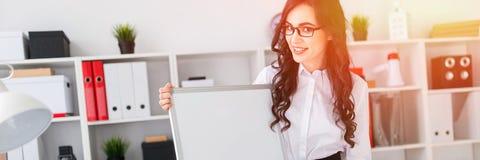 Het mooie jonge meisje bevindt zich dichtbij een bureau en richt met een pen op een lege raad stock foto's