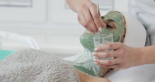 Het mooie jonge meisje bij de schoonheidsspecialist doet de kuuroordprocedures De vrouw wordt gewassen van het groene gezichtsmas stock footage