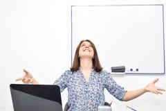 Het mooie jonge meisje in het bureau kijkt omhoog, dient het uitspreiden van haar in stelt van de voltooiing van meditatie en gli stock afbeeldingen