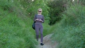 Het mooie jonge meisje daalt een weg op een heuvelhoogtepunt van groen gras stock video