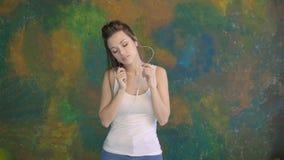 Het mooie jonge meisje dansen Hij luistert aan muziek op hoofdtelefoons Zeer aardige bewegingen stock video