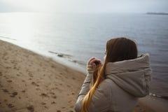 Het mooie jonge meisje die in de winterjasje aan de winterzonsondergang door rivier kijken en verwarmt koude handen ademhaling royalty-vrije stock foto