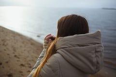 Het mooie jonge meisje die in de winterjasje aan de winterzonsondergang door rivier kijken en verwarmt koude handen ademhaling royalty-vrije stock foto's