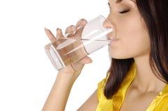 Het mooie jonge meisje drinkt water van glas Stock Foto