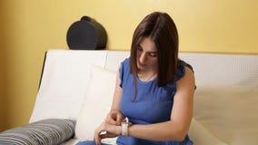 Het mooie jonge meisje in een blauw kostuum zit op de laag en plaatst een witte klok op haar hand stock videobeelden