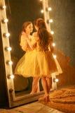 Het mooie jonge meisje in een gouden avondjurk bevindt zich op een bontdeken dichtbij een grote spiegel in een kader met lichten  stock afbeeldingen