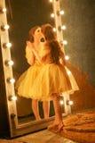 Het mooie jonge meisje in een gouden avondjurk bevindt zich op een bontdeken dichtbij een grote spiegel in een kader met lichten  royalty-vrije stock foto's