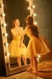 Het mooie jonge meisje in een gouden avondjurk bevindt zich op een bontdeken dichtbij een grote spiegel in een kader met lichten  royalty-vrije stock afbeeldingen
