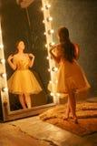 Het mooie jonge meisje in een gouden avondjurk bevindt zich op een bontdeken dichtbij een grote spiegel in een kader met lichten  stock foto's