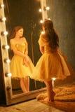 Het mooie jonge meisje in een gouden avondjurk bevindt zich op een bontdeken dichtbij een grote spiegel in een kader met lichten  royalty-vrije stock afbeelding