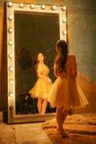 Het mooie jonge meisje in een gouden avondjurk bevindt zich op een bontdeken dichtbij een grote spiegel in een kader met lichten  royalty-vrije stock foto