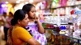 Het mooie jonge meisje en grootmoeder zoeken en kiest een gift bij winkelcomplex stock footage