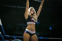 Het mooie jonge meisje glimlachen in ring, toont een teken met rond aantal Stock Fotografie