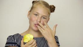 Het mooie jonge meisje kleedde zich in een gestreepte kleding etend een appel gezond voedsel - sterk tandenconcept stock videobeelden