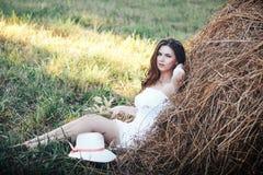 Het mooie jonge meisje ligt op hooiberg Stock Foto's