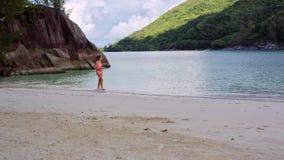 Het mooie jonge meisje loopt het strand in de lagune op de Seychellen stock videobeelden