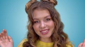 Het mooie jonge meisje met lang blond haar opent haar wapens en toont een gezicht Close-up stock footage
