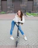 Het mooie jonge meisje met lang bruin haar hield terwijl het berijden van de autoped om aan een vriend op de telefoon op de achte Royalty-vrije Stock Foto's