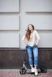 Het mooie jonge meisje met lang bruin haar hield terwijl het berijden van de autoped op de achtergrond van de grijze muur op Zij  stock foto